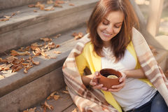 Young woman resting and drinking tea sitting in autumn garden on the steps, wrapped in a woolen plaid blanket. Royalty Free Stock Images
