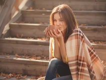Young woman  resting and drinking tea sitting in autumn garden on the steps, wrapped in a woolen plaid blanket. Stock Photos