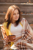 Young woman resting and drinking tea sitting in autumn garden on the steps, wrapped in a woolen plaid blanket. Stock Image