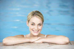 Young Woman Resting On Edge Of Swimming Pool. Smiling at camera Royalty Free Stock Photos