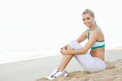 Young Woman Resting After Exercise On Beach Royalty Free Stock Photos