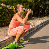 Young woman resting after exercising and holding water bottle Royalty Free Stock Images
