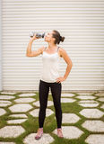 Young woman resting after exercising and holding water bottle Royalty Free Stock Photos
