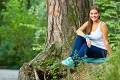 Young woman resting in forest. Green wild wood background. Smiling beautiful sporty girl Royalty Free Stock Photography