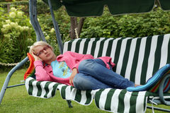 Young woman resting in a garden chair Royalty Free Stock Photography