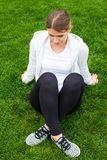 Resting after workout in the park. Young woman resting on the green grass after a workout session in the park Stock Images
