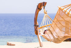 Young woman resting in hammock near the sea Stock Photos