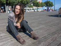 Young woman resting on harbor pier in Barcelona. Young woman is resting in the beautiful sun on the pier of the Barcelona harbor Royalty Free Stock Photo
