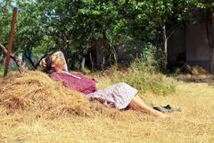 Young woman resting on a haystack Royalty Free Stock Photography