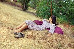 Young woman resting on a haystack Stock Photo