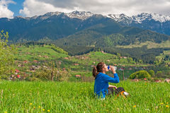 Young woman resting on hill with beautiful mountain scenery on background Stock Image