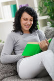 Young woman resting at home, reading a book Royalty Free Stock Photography