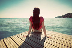 Young woman resting on jetty looking at the calm sea on sunny summer day. Stock Photos