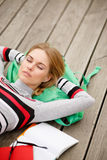 Young woman resting lying head on backpack Stock Images