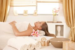 Young woman resting on massage bed at spa. Stock Photo