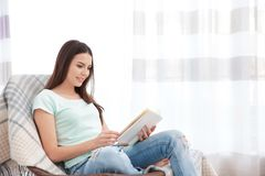 Young woman resting on modern chair and reading book. At home in light room Royalty Free Stock Photos