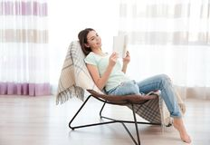 Young woman resting on modern chair and reading book at home. In light room Stock Photography
