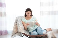 Young woman resting on modern chair and reading book. At home in light room Stock Image
