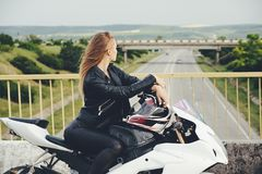 Young woman thinking of new destinations while sitting on bike. Young woman resting on a motorbike while looking over bridge on the road. Security on the roads Royalty Free Stock Image
