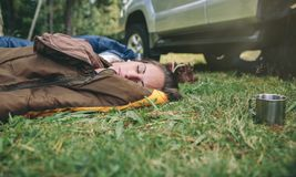 Young woman resting in the nature on sleeping bag. Closeup of young beautiful woman sleeping in the nature inside of sleeping bag over the grass Royalty Free Stock Photography