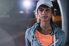 Young woman resting after night fitness in the city. Close up shot of young woman resting after night fitness in the city. African female in sportswear looking Stock Photography