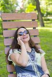 Young woman resting in the park on the bench. Beautiful female relaxing on a park bench and using a smartphone. toned stock image