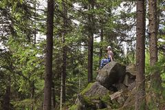 Young woman resting on rocks. In beautiful forest stock photography