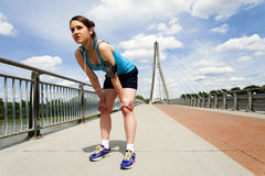Young woman resting after run. in blue sportswear. over the brid Stock Images