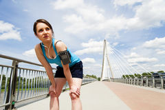 Young woman resting after run. in blue sportswear. over the brid Stock Image
