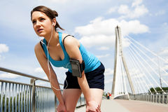 Young woman resting after run. in blue sportswear. over the sky Royalty Free Stock Images