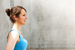 Young woman resting after run by the wall in city with big smile Royalty Free Stock Photo