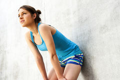 Young woman resting after run by the wall in city with big smile Royalty Free Stock Photos