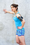 Young woman resting after run by the wall in city with big smile Royalty Free Stock Images