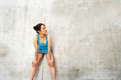 Young woman resting after run by the wall in city. in blue sport Stock Photo