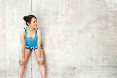 Young woman resting after run by the wall in city. in blue sport Stock Photography