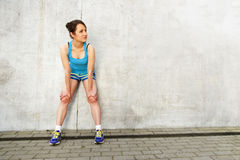 Young woman resting after run by the wall in city. in blue sport Royalty Free Stock Photo