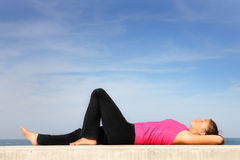 Young woman resting by the sea Royalty Free Stock Image