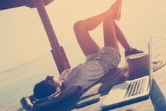 Young woman resting in shadow shelter with laptop and listening music. Intentional sun glare and vintage color Royalty Free Stock Image