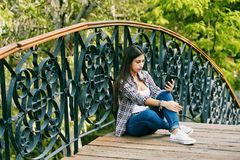 Young woman resting sitting on a wooden bridge stock photo