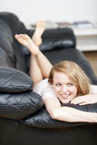 Young woman resting on sofa Stock Images