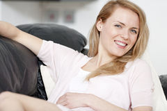 Young woman resting on sofa Royalty Free Stock Images
