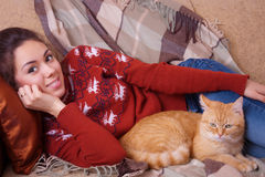 Young woman resting on sofa with a cat Stock Photo