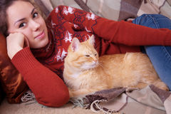 Young woman resting on sofa with a cat Royalty Free Stock Images