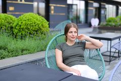 Young woman resting at street cafe and sitting near green plant. Young woman resting at street cafe and sitting in chair near green plant. Concept of beauty and Stock Images