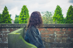 Young woman resting by wall in garden Royalty Free Stock Photo