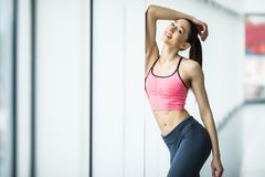 Young woman resting after workout at gym near window. Fitness female taking break after training session in health club. Young woman resting after workout at Stock Photography