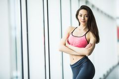 Young woman resting after workout at gym near window. Fitness female taking break after training session in health club. royalty free stock images