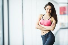 Young woman resting after workout at gym near window. Fitness female taking break after training session in health club. Young woman resting after workout at Royalty Free Stock Photos