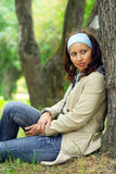 Young woman rests. Young cheerful woman in a park sitting under big tree Royalty Free Stock Photo