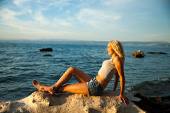 Young woman rests on the beach on a hot summer day.  Stock Images